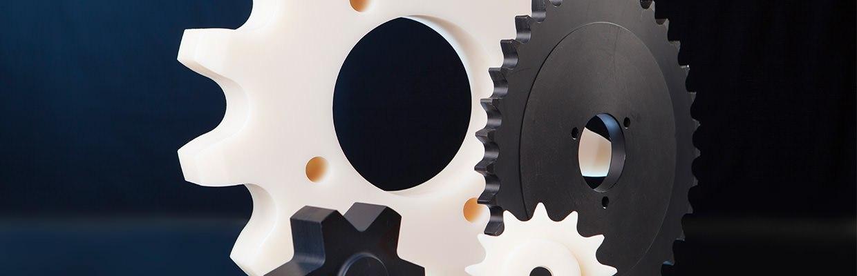 Unterschiedliche Förderelemente, wie ein Zahnrad, ein Kettenrad und ein Kettensegment aus technischen Kunststoffen.